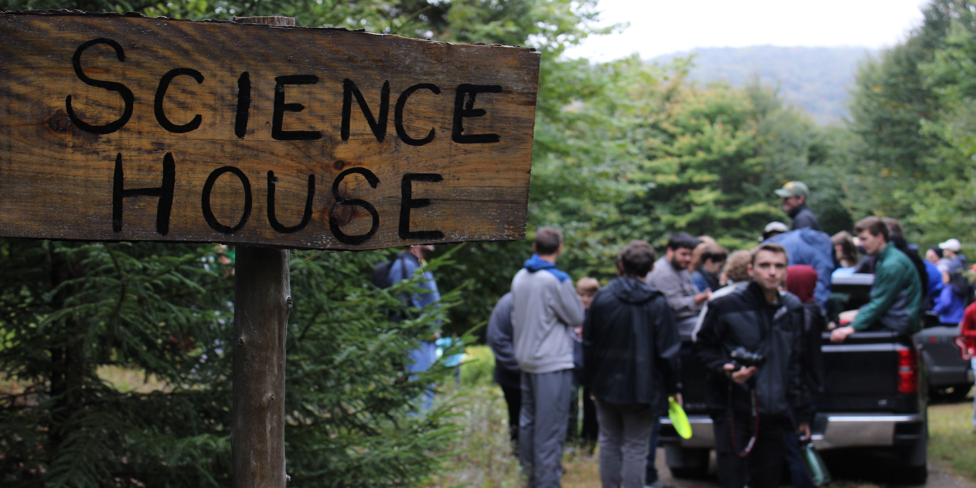 A sign that reads Science House with CSHers in the background. Taken at Fall Camping 2019