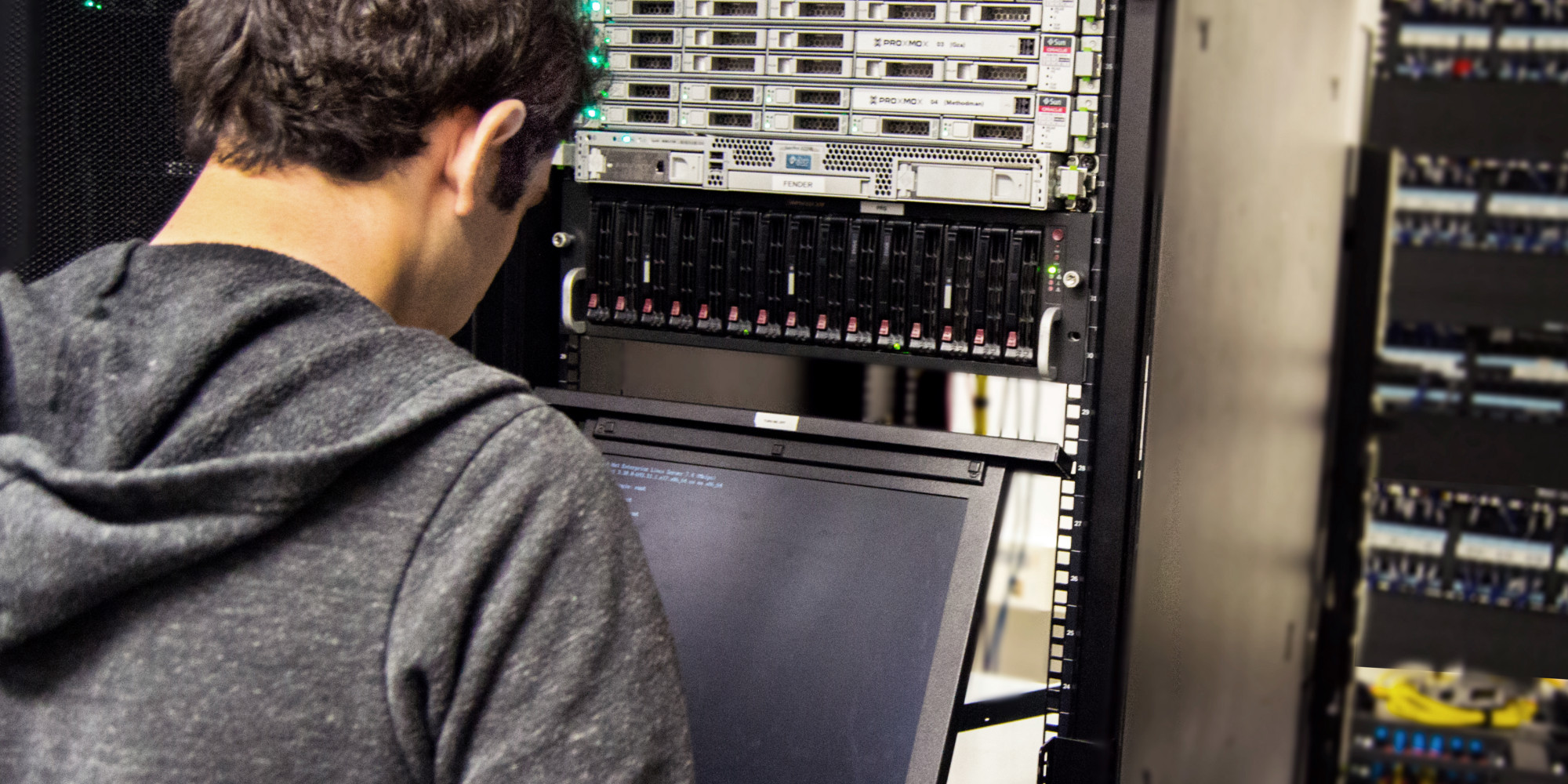 A CSH member stands at a terminal in the CSH server room